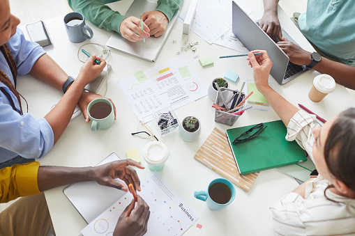 High angle view at contemporary creative team working together at cluttered table with coffee mugs and documents, teamworking or studying concept, copy space
