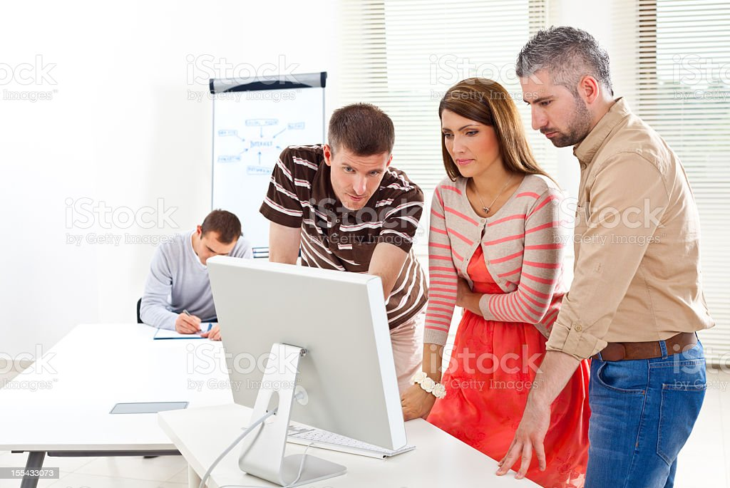 Business team at work Three colleagues watching new project on the computer. 30-34 Years Stock Photo
