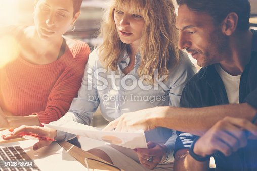 912675036istockphoto Business team at working process.Young professionals work with new market project. Project managers meeting.Blurred background.Horizontal.Flares. 912673594