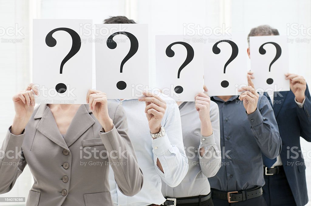 Business team behind question marks stock photo