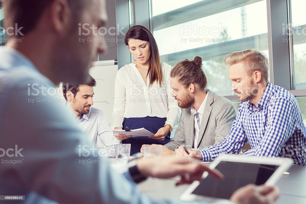 Business team brainstorming in a board room Focus on business team having meeting in a board room in an office, sitting at the conference table and discussing. In the foreground blured businessman using a digital tablet.  2015 Stock Photo