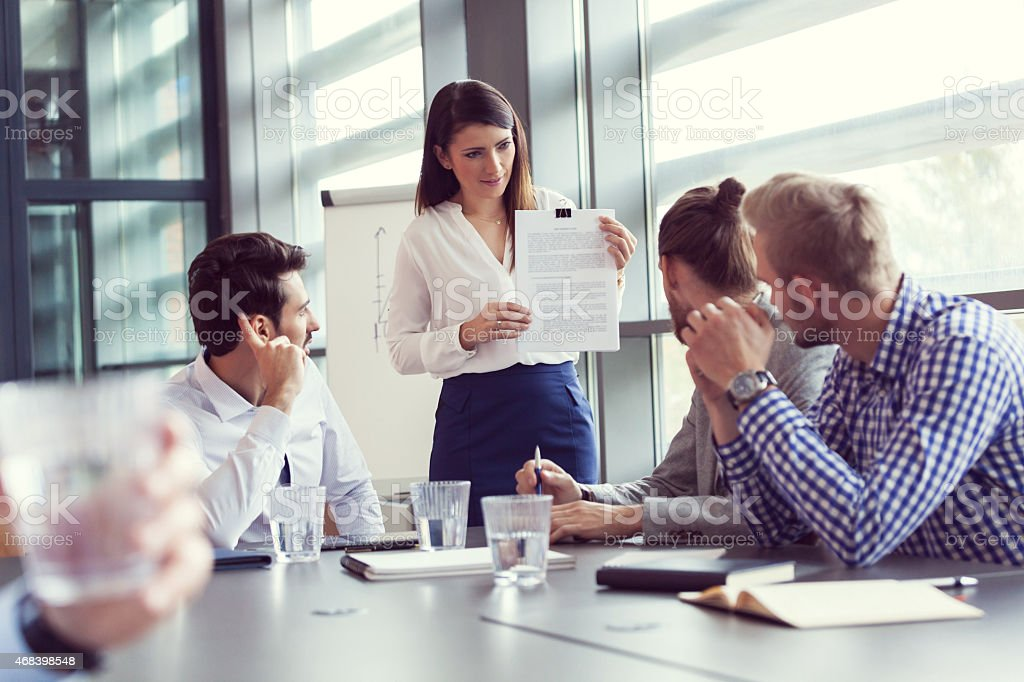 Business team brainstorming in a board room Business team having meeting in a board room in an office, sitting at the conference table and discussing. Businesswoman holding an greement in hands.  2015 Stock Photo