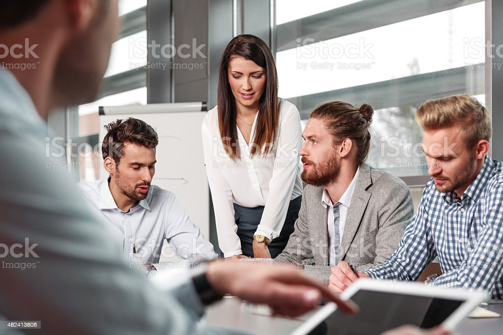 Business team brainstorming in a board room Business team having meeting in a board room in an office, sitting at the conference table and discussing. In the foreground blured businessman using a digital tablet.  2015 Stock Photo