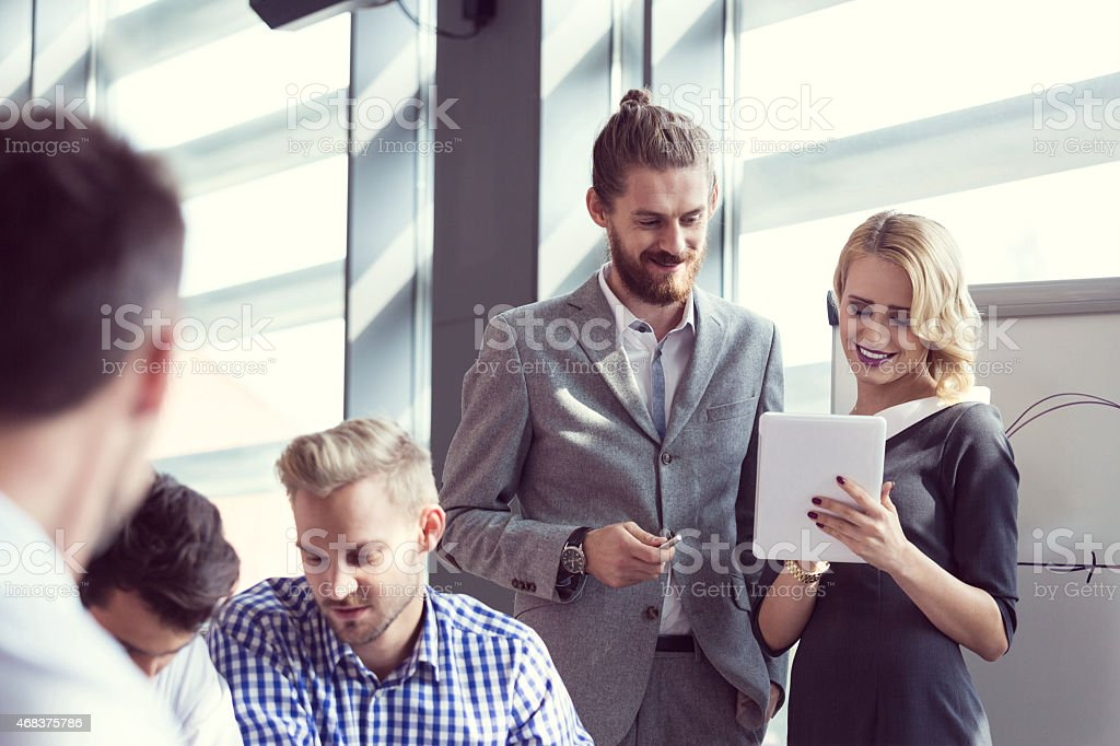 Business team brainstorming in an office Group of business people having meeting in a board room in an office, discussing new strategy of their company. Beautiful bonde woman holding a digital tablet and talking with bearded man wearing suit. Flipchart behind them. 2015 Stock Photo