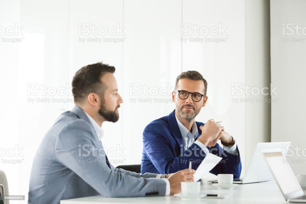 Business team brainstorming in meeting Mature businessman paying attention to the discussion during meeting. Team of professionals during meeting in conference room. Adult Stock Photo