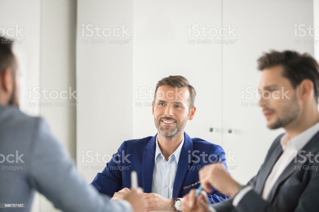 Business team brainstorming new ideas Mature businessman discussing new plan with colleagues in meeting. Business team brainstorming new ideas. Adult Stock Photo