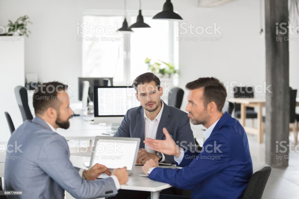 Business team brainstorming over new strategy in meeting Mature businessman sharing his views with colleagues in meeting. Business team brainstorming over business strategy in meeting. Adult Stock Photo