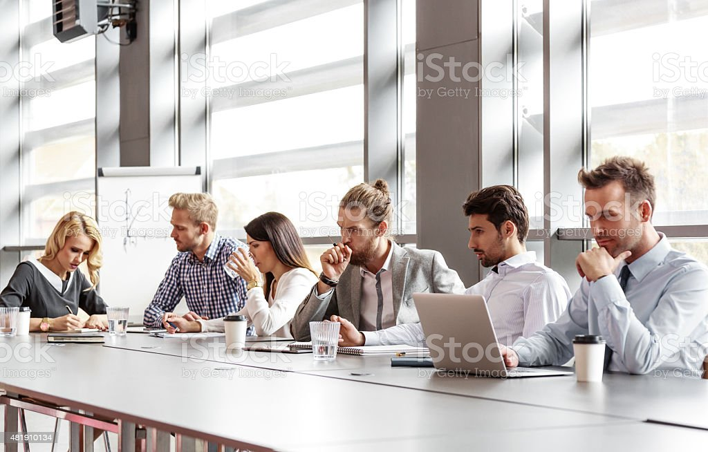 Business team collaborating in board room Group of business people - women and men - having meeting in a board room in an office, sitting at the table discussing new strategy of their company, brainstorming, using laptop and collaborating. Flipchart in the background. 2015 Stock Photo