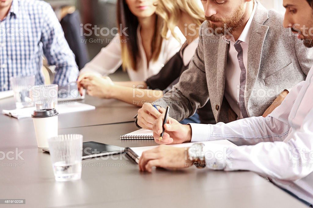 Business team collaborating Group of businessmen having meeting in a board room in an office, sitting at the conference table brainstorming, collaborating and writting notes.  2015 Stock Photo
