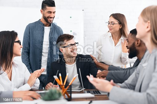 istock Business team congratulating man with successful project 1084111528