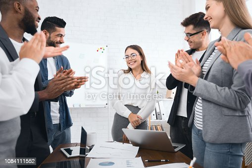 913332100 istock photo Business team congratulating successful female manager with applause 1084111552