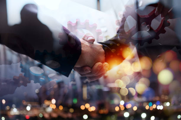 Business team connect pieces of gears. Handshake overlay. Teamwork, partnership and integration concept - foto stock