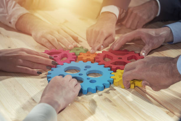 Business team connect pieces of gears. Teamwork, partnership and integration concept stock photo