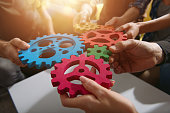 istock Business team connect pieces of gears. Teamwork, partnership and integration concept 1212507783