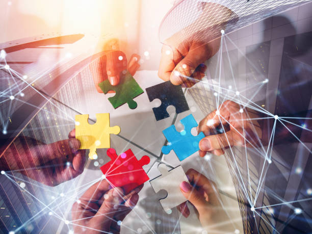 Business team connect pieces of puzzles. Teamwork, partnership and integration concept. double exposure with network effects stock photo