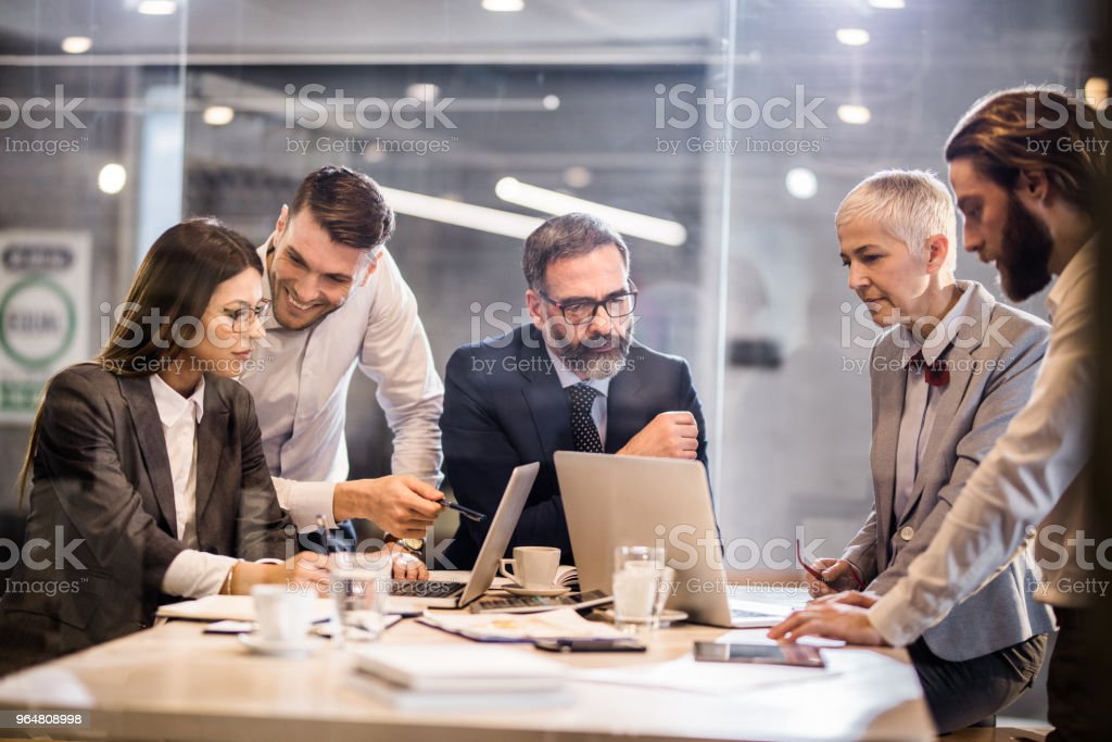 Business team cooperating while working on laptops in the office. royalty-free stock photo
