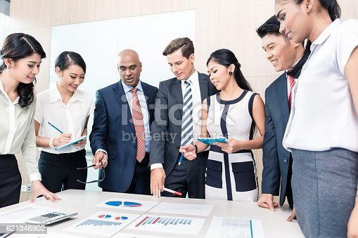 istock Business team discussing graphs and numbers in meeting 621348902