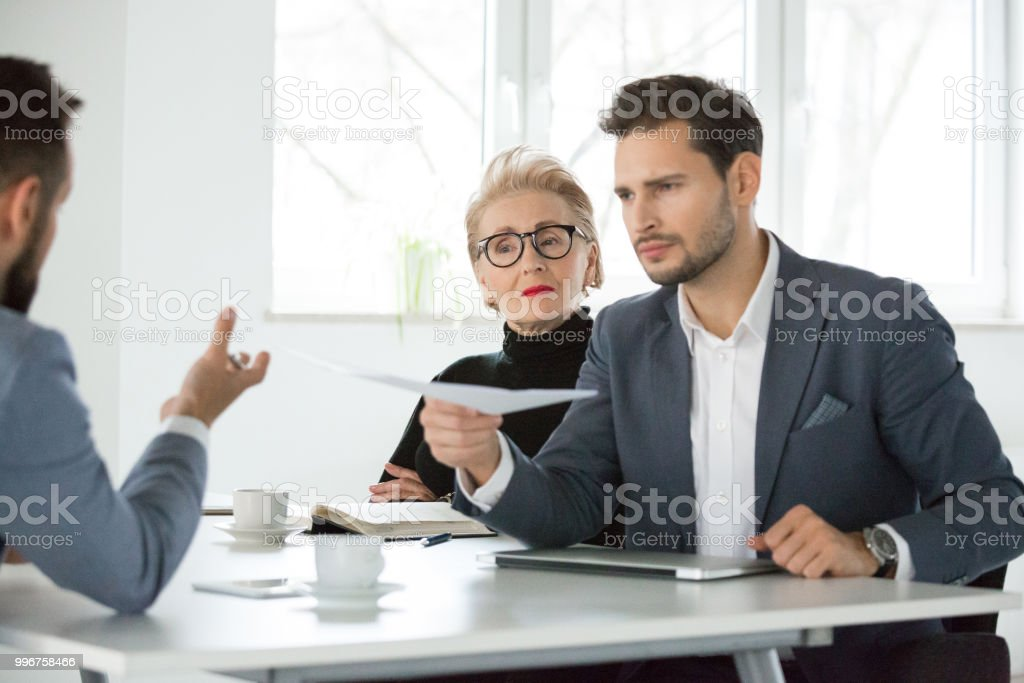 Business team discussing over contract document in meeting Young businessman giving a document to colleague during meeting. Business team discussing over contract in meeting. Active Seniors Stock Photo
