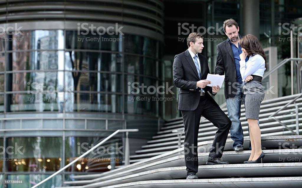 Equipe de negócios a discutir documentos ao ar livre na escada - foto de acervo