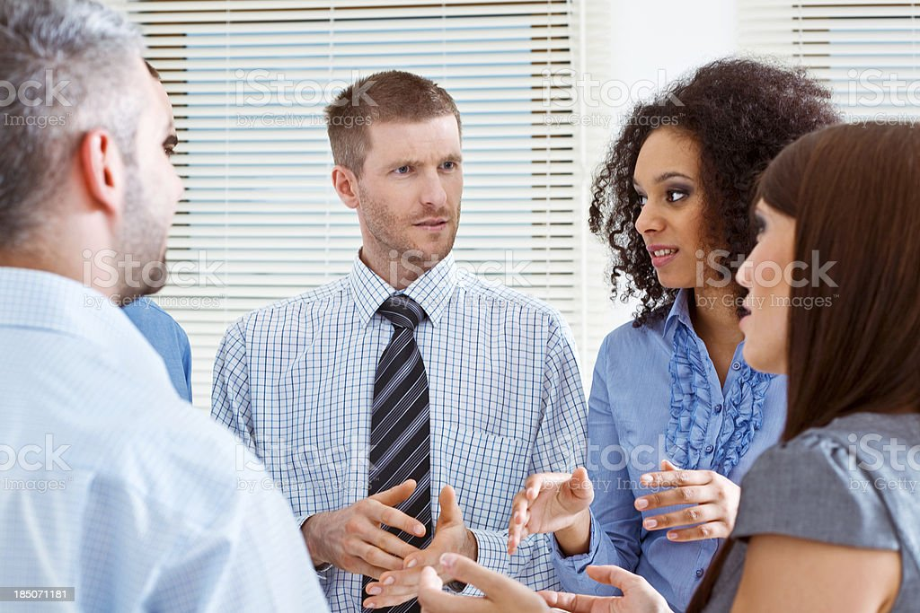 Business Team discussing Group of serious business people standing in an office and talking. 25-29 Years Stock Photo