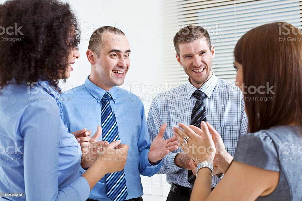 Business Team discussing Four smiling business people standing in an office and talking. 25-29 Years Stock Photo