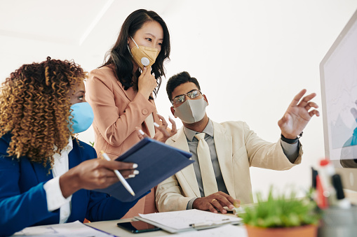 Business team in protective masks looking at chart on computer screen and discussing sales growth