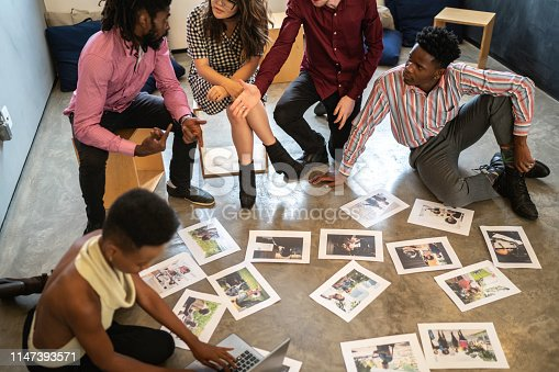 681735120istockphoto Business team discussing some papers on the floor in the office 1147393571