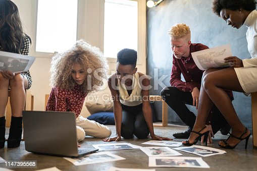 istock Business team discussing some papers on the floor in the office 1147395568