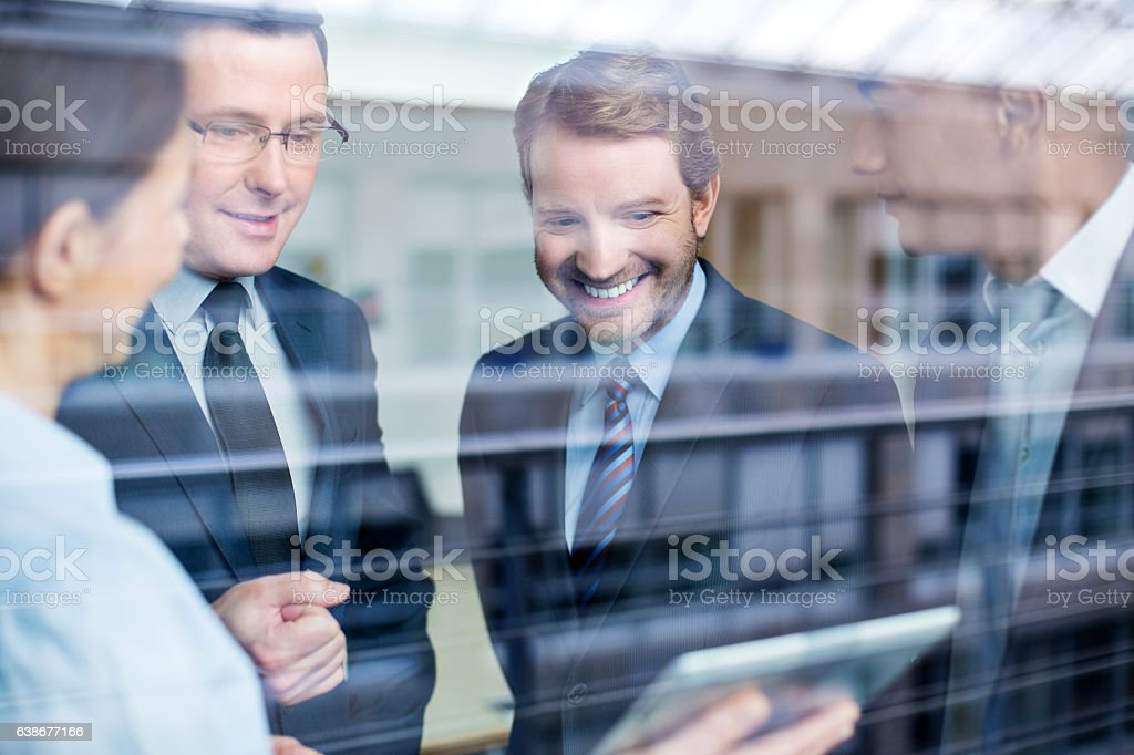 Business team discussing work on a tablet stock photo
