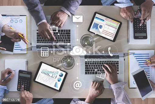 ONLINE ADVERTISING Business team hands at work with financial reports and a laptop