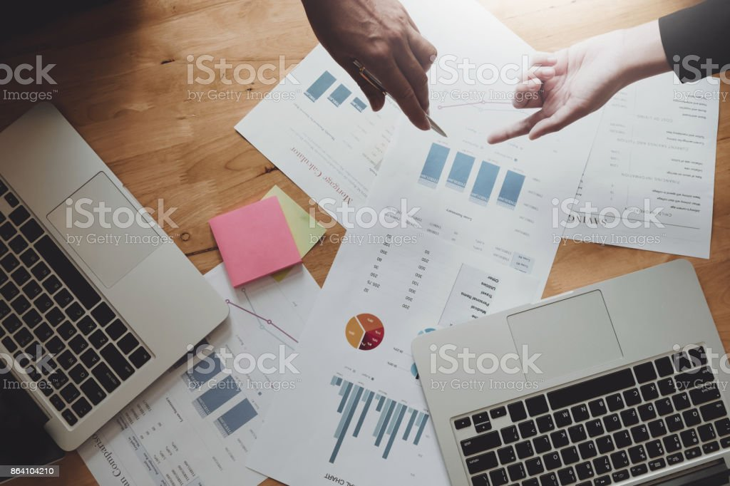 Business team hands pointing financial document for discussing and analysis new project on office wooden desk with laptop computer, Top view above shot. royalty-free stock photo