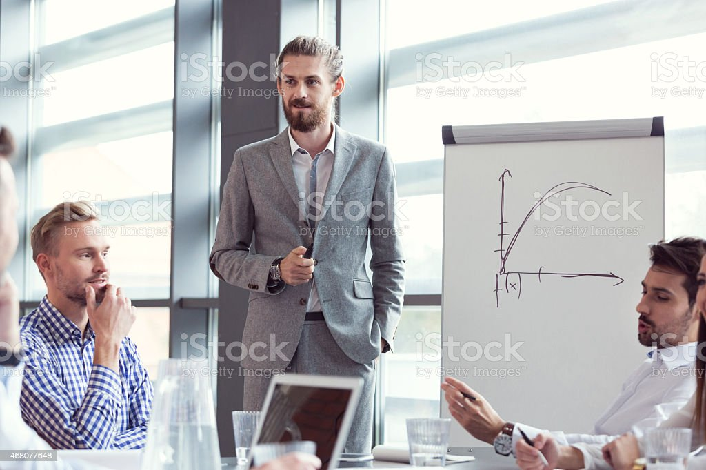 Business team having brainstorming in an office Group of businessmen having meeting in a board room in an office, discussing new strategy of their company. Bearded man wearing grey suit standing next to flipchart and giving presentation.  2015 Stock Photo