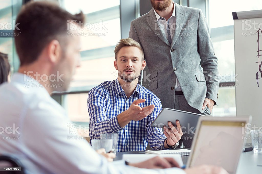 Business team having brainstorming in an office Group of businessmen having meeting in a board room in an office, discussing new strategy of their company. Focus on blonde bearded man wearing checkered shirt holding digital tablet in hand.  2015 Stock Photo