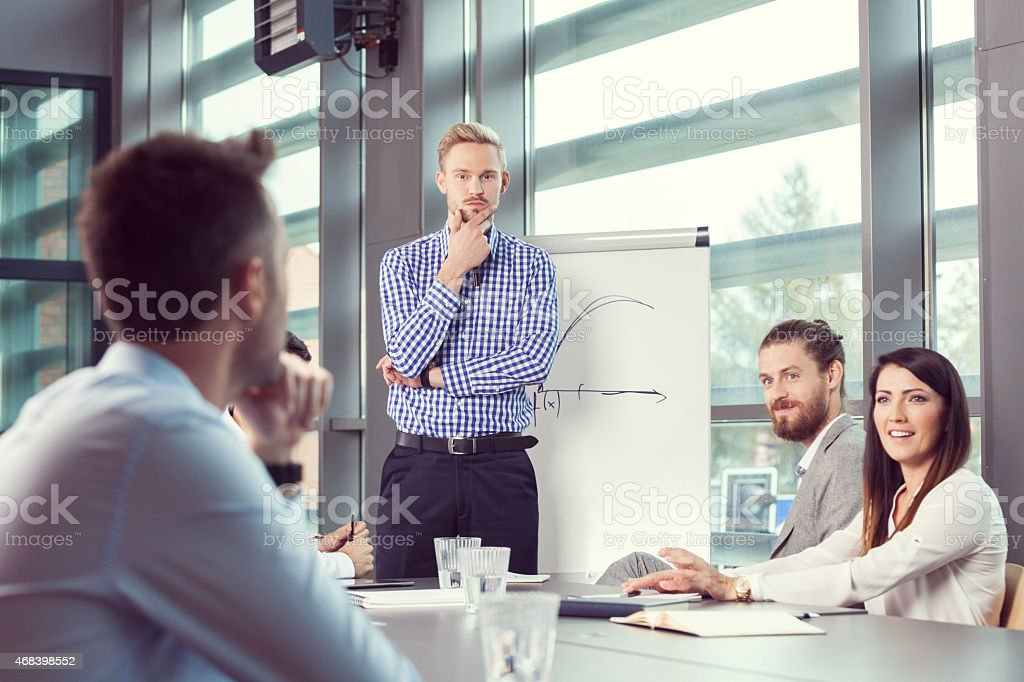 Business team having brainstorming in an office Group of businessmen having meeting in a board room in an office, discussing new strategy of their company. Bearded man wearing checkered shirt next to flipchart. 2015 Stock Photo
