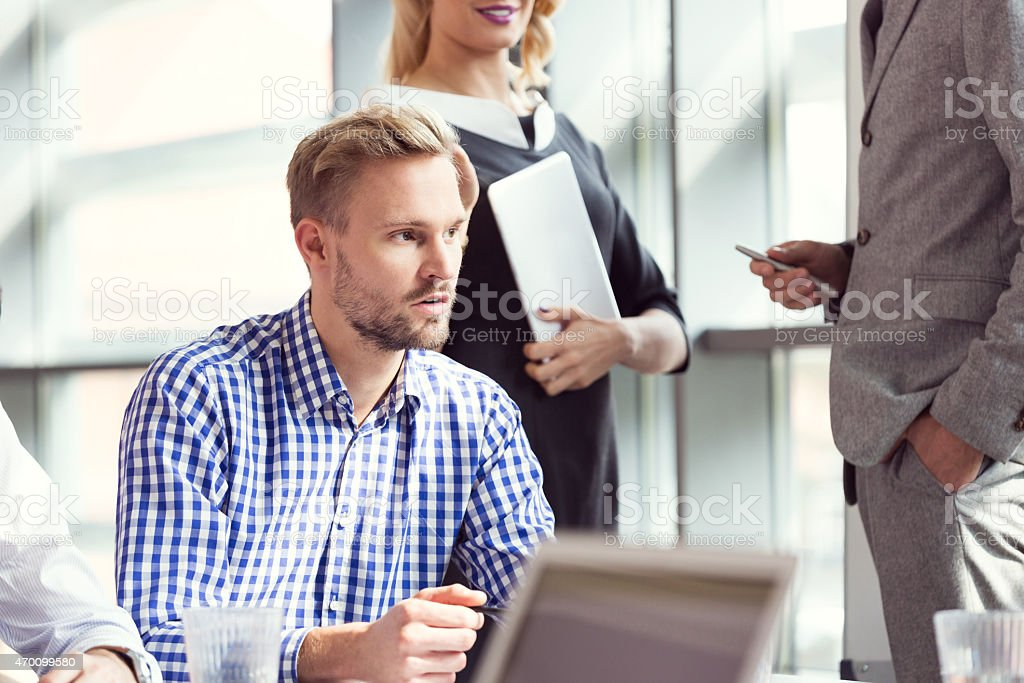 Business team having brainstorming in an office Group of business people having meeting in a board room in an office. Focus on blonde bearded man wearing checkered shirt. 2015 Stock Photo