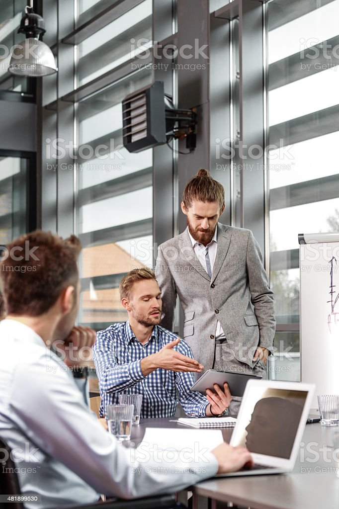 Business team having brainstorming in an office Group of businessmen having meeting in a board room in an office, discussing new strategy of their company. Bearded man wearing grey suit standing next to flipchart and talking with his colleague. On foreground man using laptop. 2015 Stock Photo