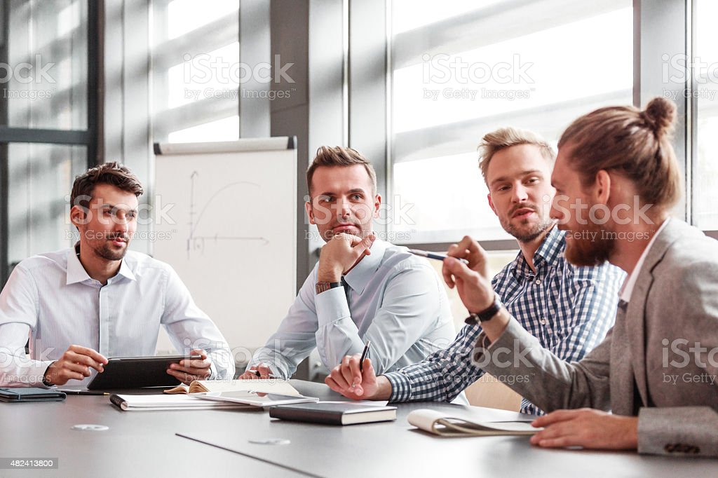 Business team having meeting in a board room Group of businessmen working in a board room at the conference table in an office together, discussing, branstorming. Flipchart in the background. 2015 Stock Photo