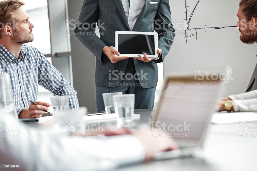 Business team having meeting in a board room Group of businessmen working in a board room at the conference table in an office together. Man standing next to flipchart holding digital tablet. In the foreground blured man using laptop. 2015 Stock Photo