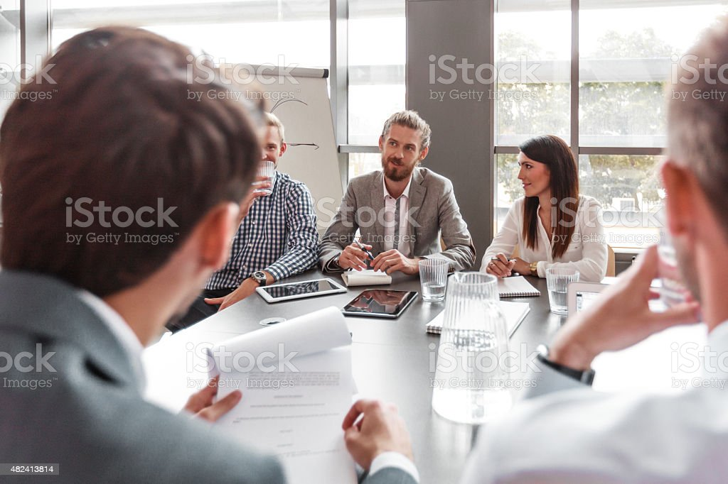 Business team having meeting in a board room Group of business people working in a board room at the conference table in an office together, discussing, branstorming.  2015 Stock Photo
