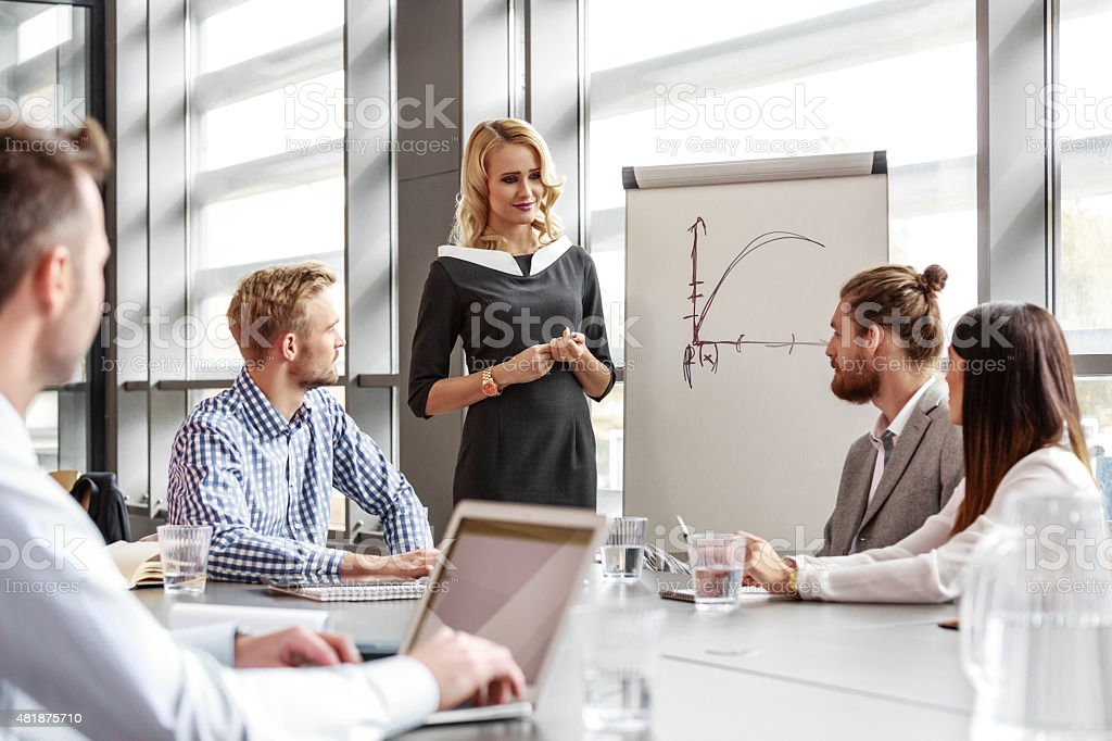 Business team having meeting in an office Group of business people having meeting in a board room in an office, discussing new strategy of their company. An attractive businesswoman wearing grey dress standing next to flipchart and giving presentation.  2015 Stock Photo