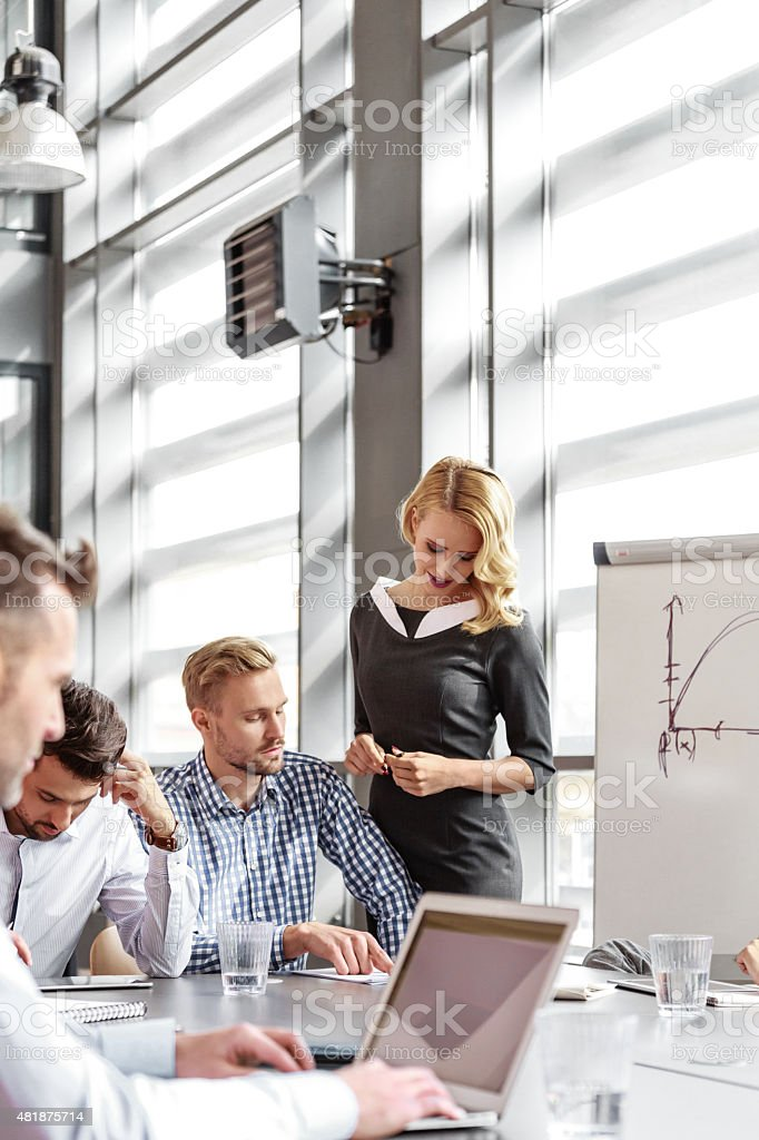 Business team having meeting in an office Group of business people having meeting in a board room in an office, discussing new strategy of their company. An attractive businesswoman wearing grey dress standing next to flipchart and talking with his business partner.  2015 Stock Photo