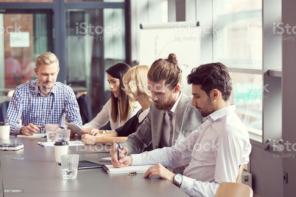 Business team having meeting in an office Group of business people having meeting in a board room, sitting at the conferecne table and taking notes. 2015 Stock Photo