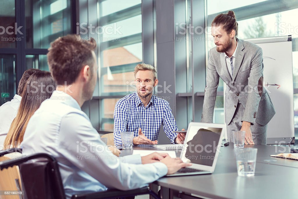 Business team having meeting in an office Group of business people having meeting in a board room, discussing new strategy of their company. Businessman using laptop sitting in a wheelchair. 2015 Stock Photo
