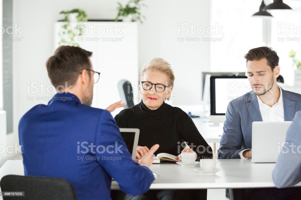 Business team having meeting in modern office space Senior businesswoman listening to male colleague during a meeting. Business team having meeting in modern office space. Active Seniors Stock Photo