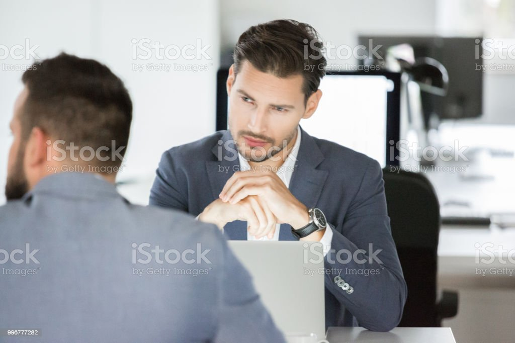 Business team having meeting in office. Young businessman meeting with colleagues at office. Business team having meeting in office. Adult Stock Photo