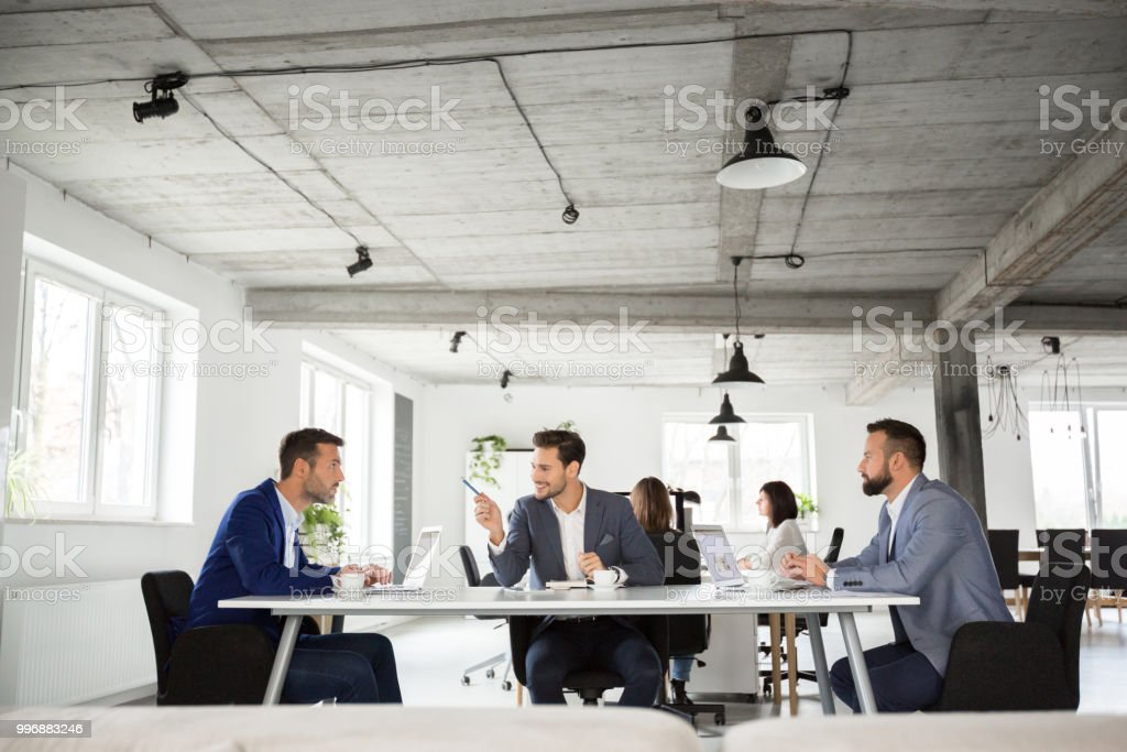 Business team having meeting in office Business team sitting at table and discussing with colleagues working in background. Adult Stock Photo