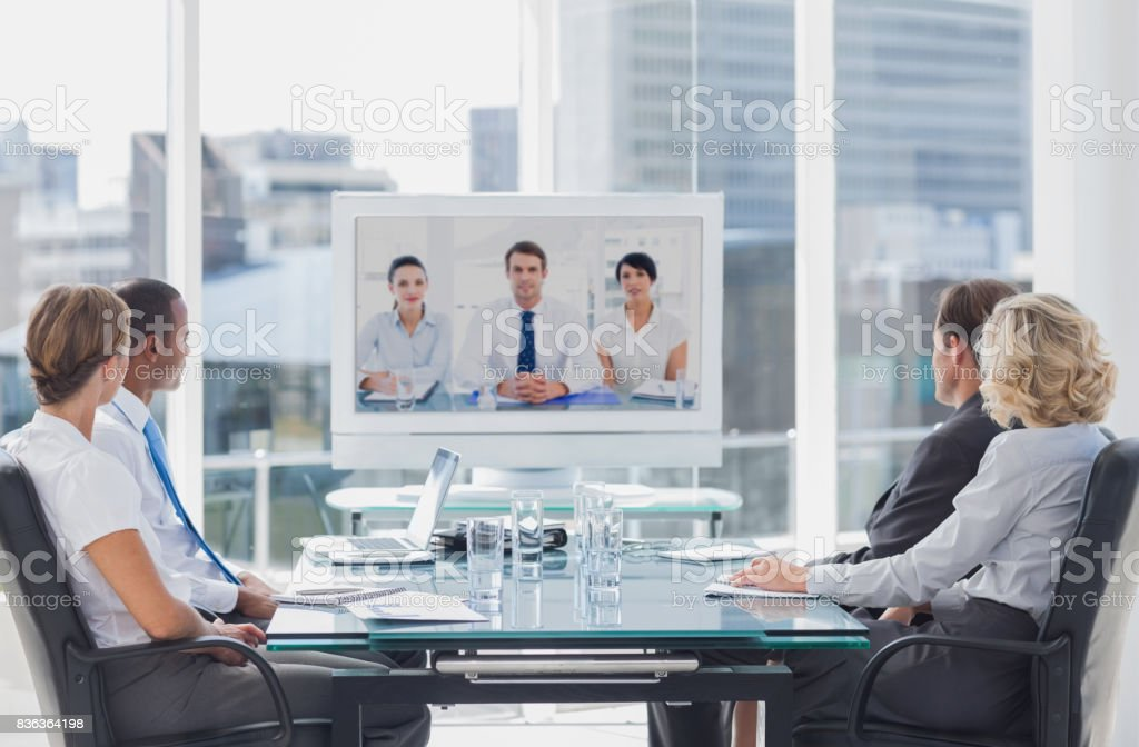 Business team having video conference with another business team in...