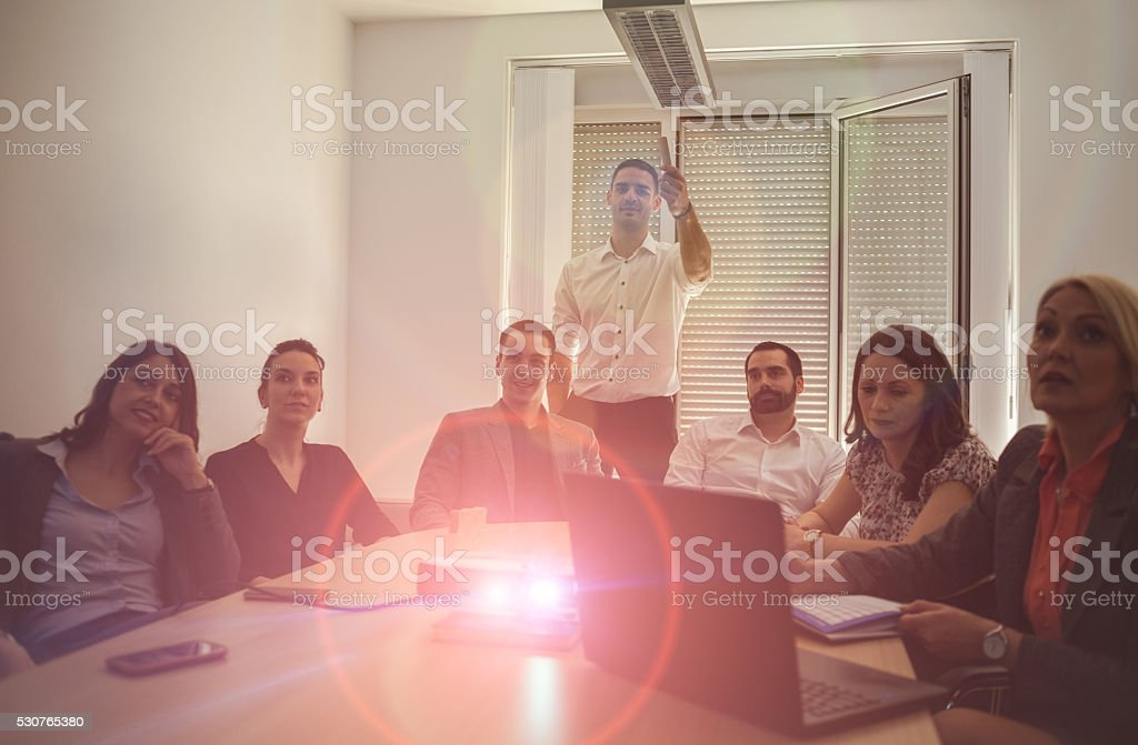 Business team in meeting room watching video presentation stock photo