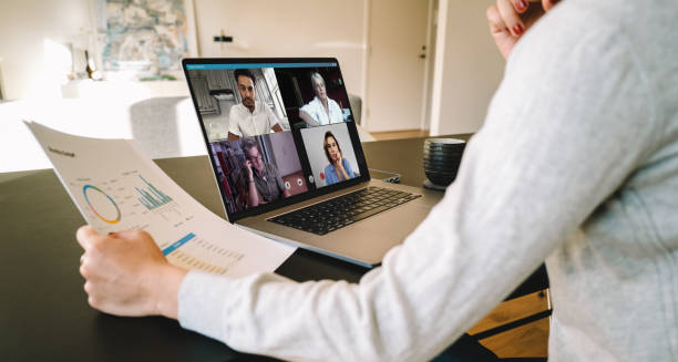 Business team in video conference Group of businessmen and businesswomen smart working from home. View from side of woman talking to her colleagues about business plan over a video conference. jacoblund stock pictures, royalty-free photos & images