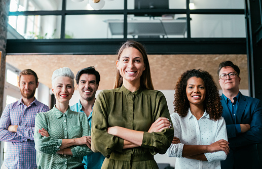 Shot of beautiful confident smiling businesswoman standing in front of her successful team.
